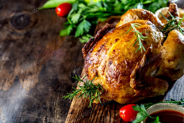 Roasted chicken with rosemary served with sauces on wooden board, selective focus, copy space.