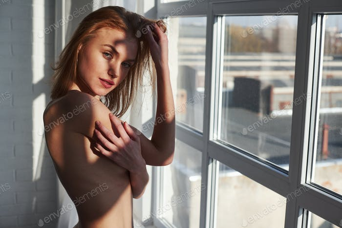 Young red haired girl with bare chest stands near the window at daytime