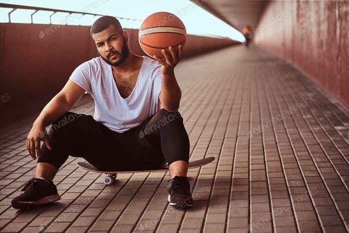 Dark-skinned guy holds a basketball while sitting on a skateboard on a footway under bridge.