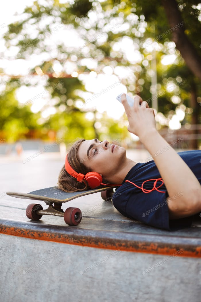 Young guy in orange headphones lying on skateboard dreamily usin