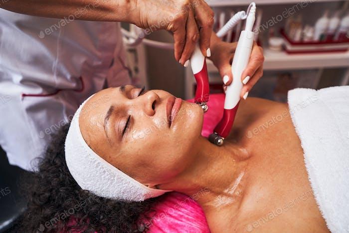 Cheerful female person enjoying professional face massage