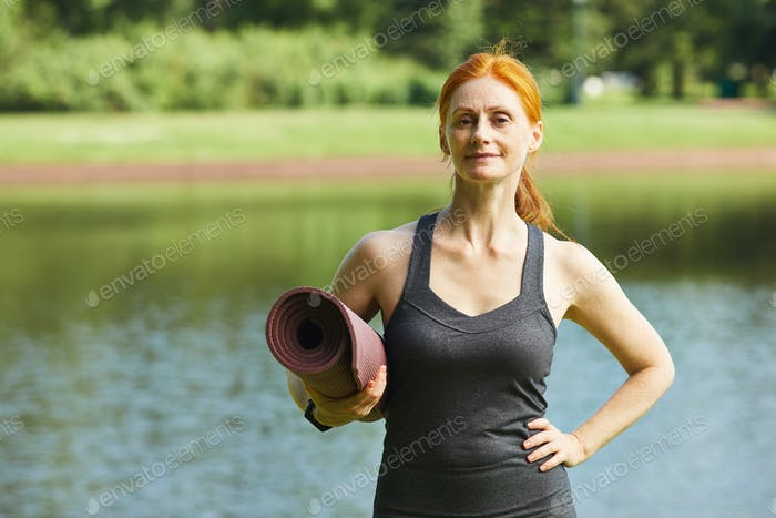 Confident woman with yoga mat