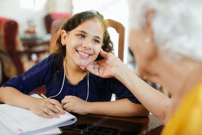 Ältere Frau helfen kleine Mädchen tun Schule Hausaufgaben
