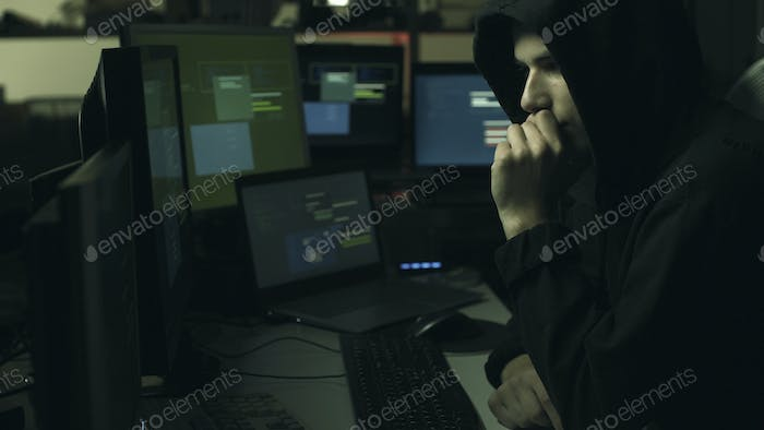 Hacker hiding in the dark and working with computers