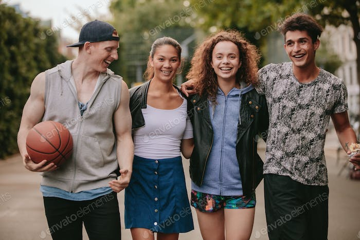 Four young friends walking together and smiling