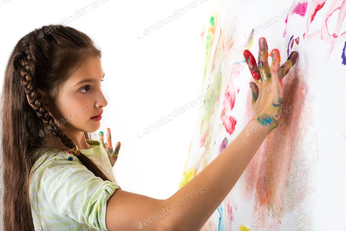 Cute girl shows paint stained hands on white
