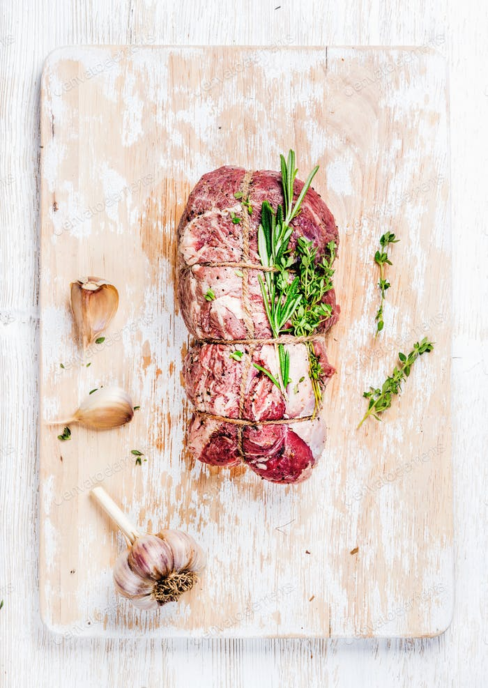 Raw roastbeef meat cut with rosemary, thyme and garlic, vertical