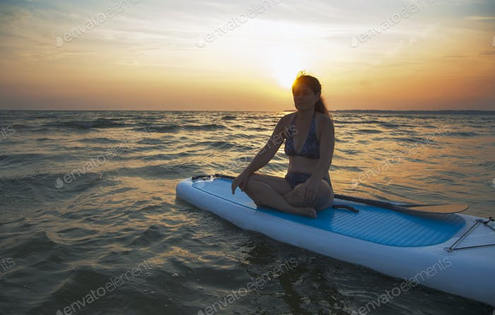 A woman seated on a paddleboard looking out at the sun setting on the horizon.