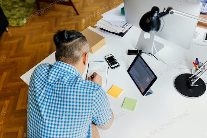 Businessman writing in notepad