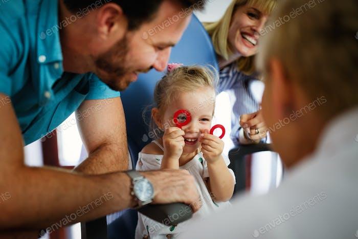 Augenarzt, Augenarzt, Augenarzt, die das Sehvermögen des Kindes auf der Suche nach Problemen und Pflege des Auges