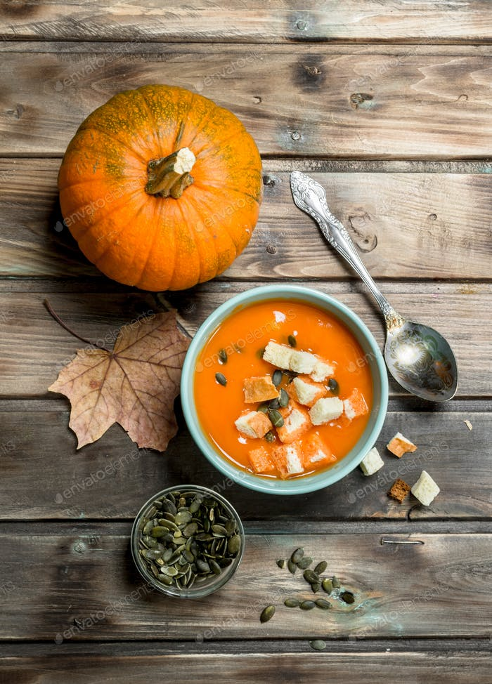 Pumpkin soup and pumpkin seeds in bowl with ripe pumpkin.
