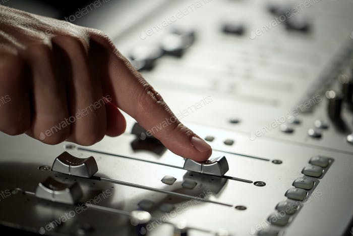 hand with mixing console in music recording studio