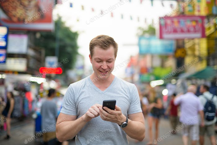 Young happy tourist man using phone against view of Khao San road in Bangkok