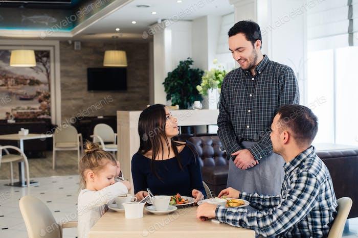 Kellner dienen Familie in einem Restaurant und bringen volle Platte