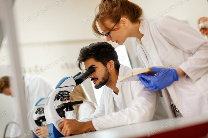Young scientists, students of chemistry working in laboratory
