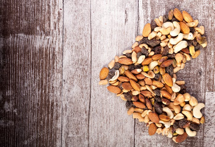 Mix of healthy raw nuts in heart shape on wooden background