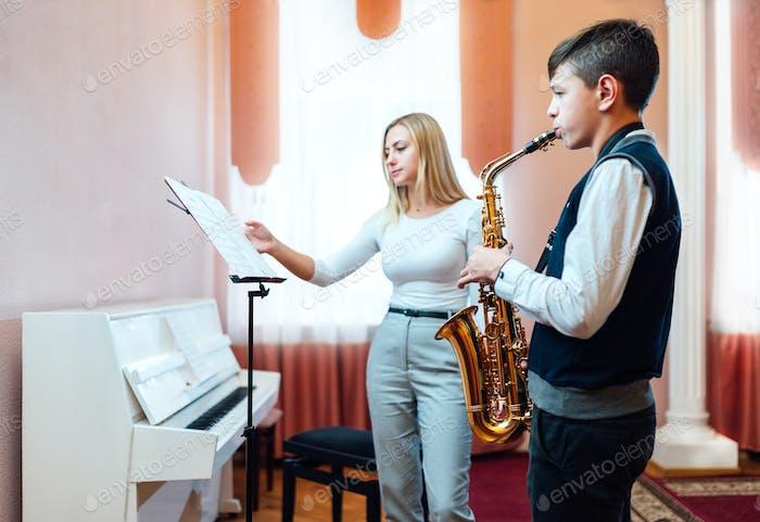 teacher turns over sheet of sheet music for student in saxophone lesson