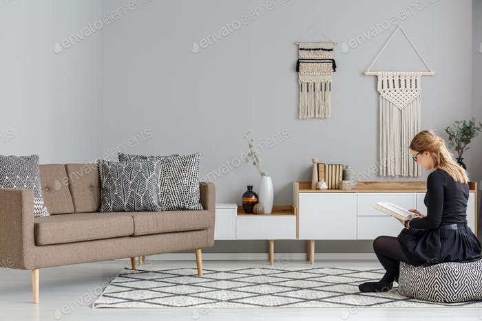 Woman on patterned pouf near brown sofa in modern living room in