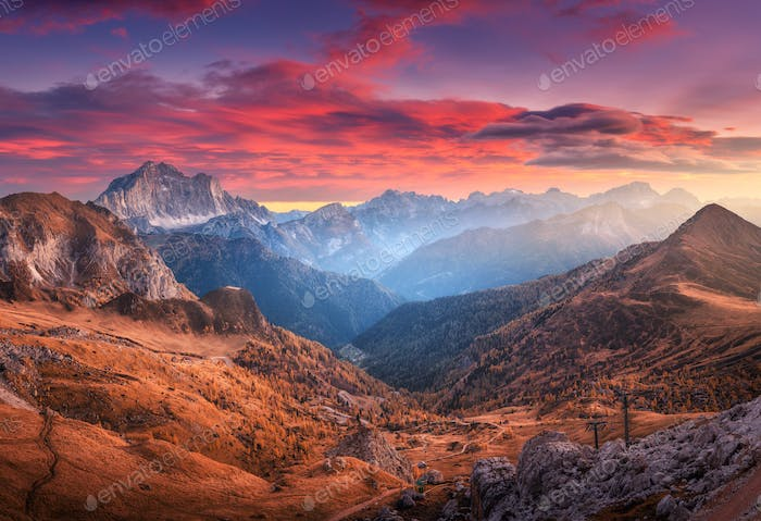 Colorful red sky with clouds over the beautiful mountains in fog