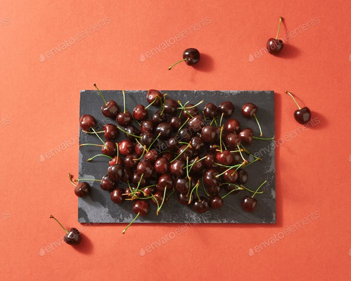 Delicious sweet cherry on a black stone board on a color background of the year 2019 Living Coral
