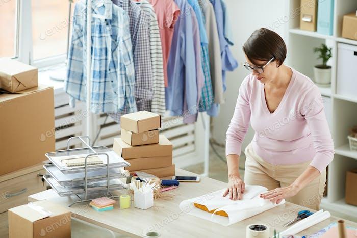 Junge Brünette Frau Verpackung gefaltet Freizeitkleidung in Papier