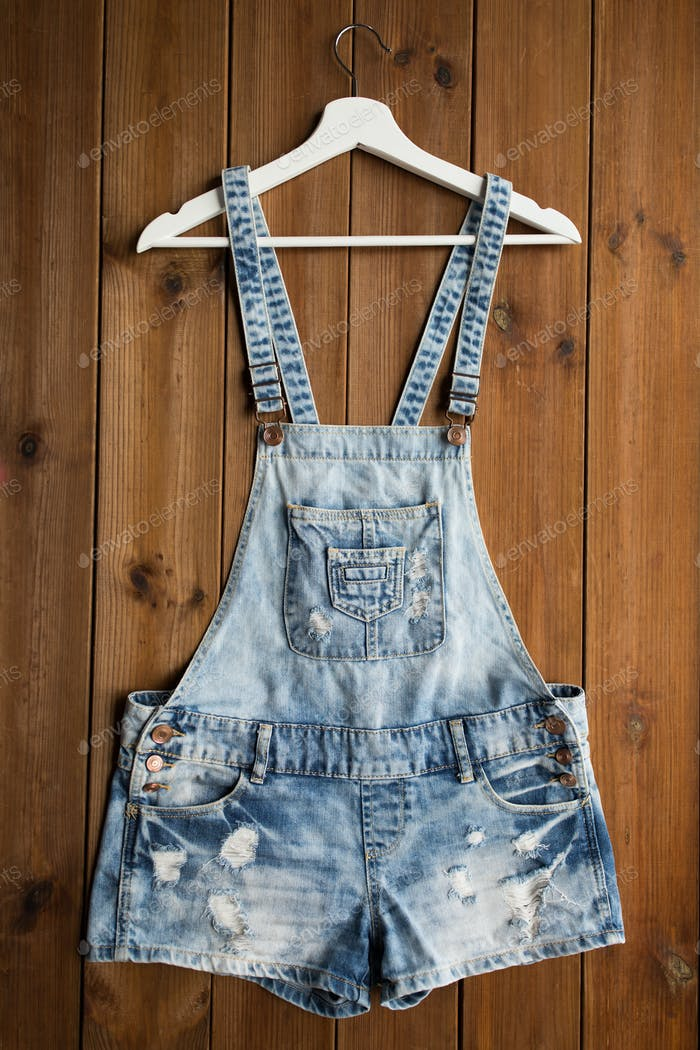 denim or jeans overalls with hanger on wood