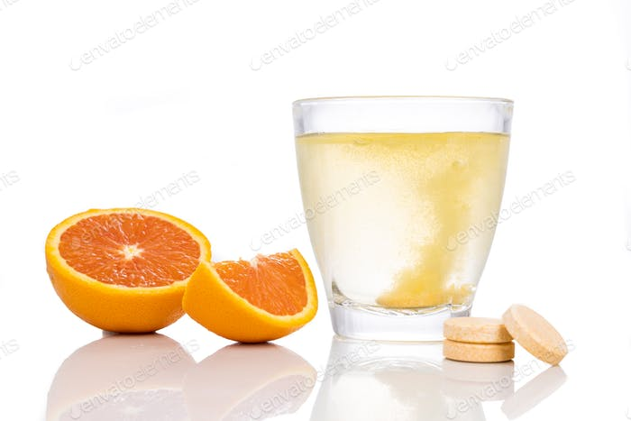 Series of orange flavored vitamin c effervescent tablet dropped and dissolve in glass of water