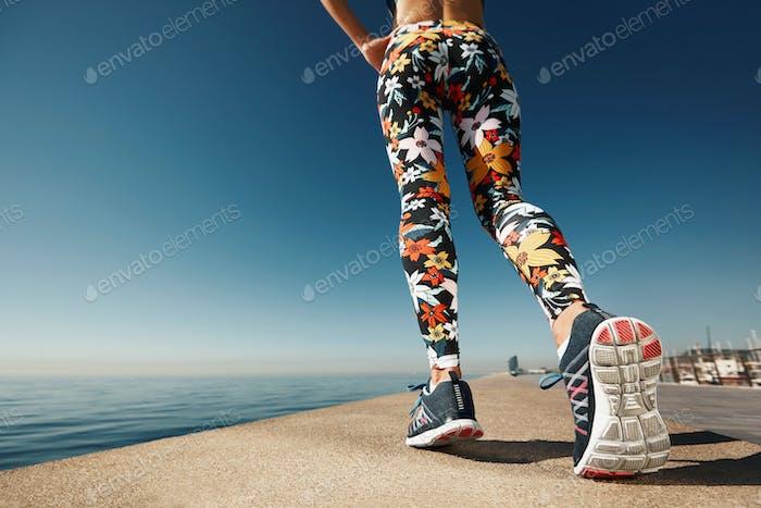 Runner woman feet running on road closeup on shoe. Female fitnes