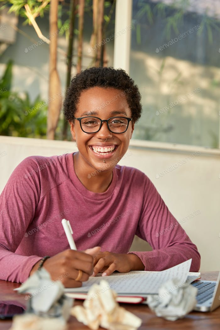 Cheerful smiling black college student works on course paper, rejoices accomplished task, holds pen