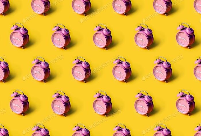 Kreatives Layout von rosa Wecker auf pastellgelbem Hintergrund. Minimales Konzept.