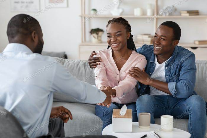 After Effective Therapy. Joyful Black Couple Handshaking With Marital Counselor After Session