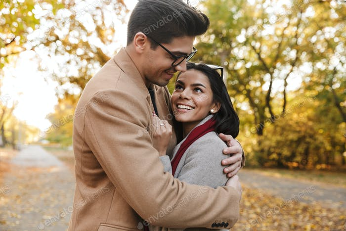 Image of charming brunette couple smiling and hugging in autumn park