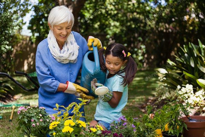 Lächelnde Großmutter und Enkelin Bewässerung Pflanzen