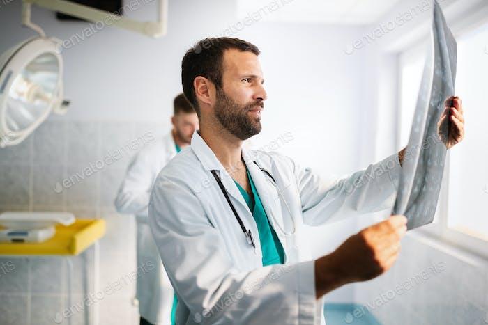 Porträt des jungen Arztes Überprüfung X-Ray im Krankenhaus, um Diagnose zu stellen