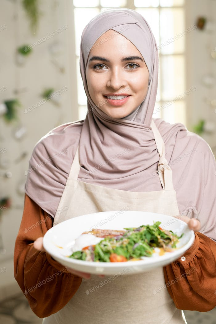 Young smiling Muslim female in hijab holding plate with selfmade salad and meat