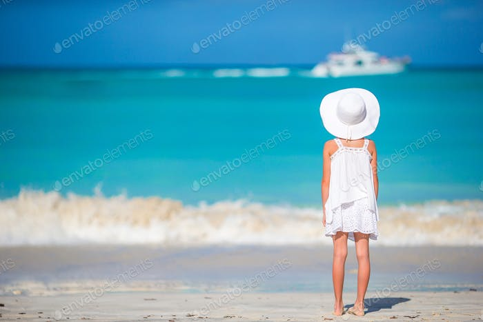 Adorable little girl in big red hat on the beach