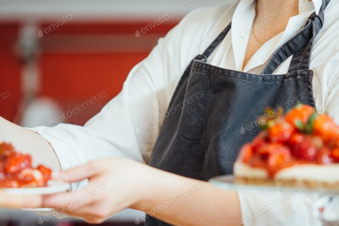 Unrecognizable confectioner holding cake on plate