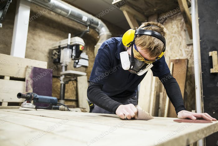 Man wearing ear protectors, protective goggles and dust mask standing in a warehouse, working on a