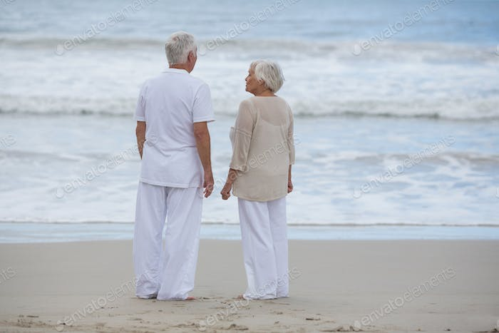 Senior couple interacting with each other on the beach