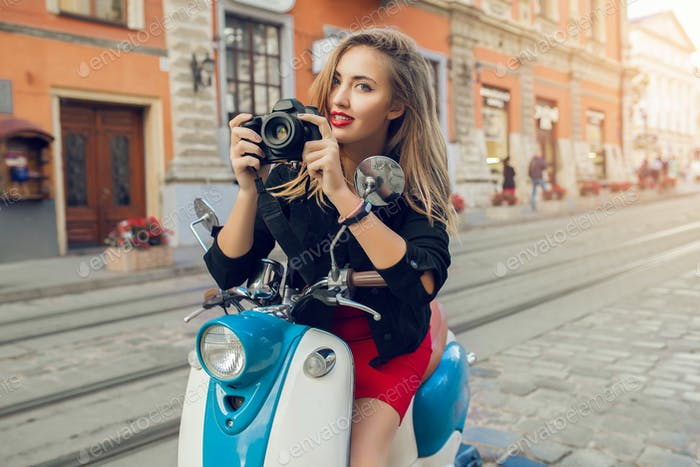young beautiful hipster woman riding with photo camera on motorbike