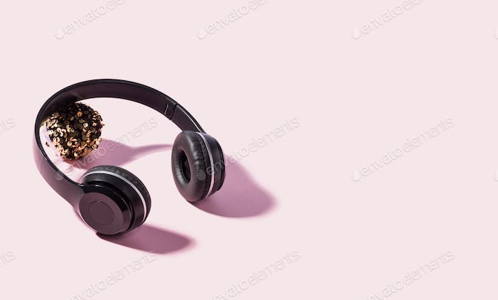 Headphones with shadow and sparkling ball on pink