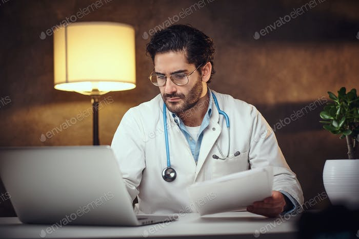 Занятый врач в своем кабинете работает с бумажными работами