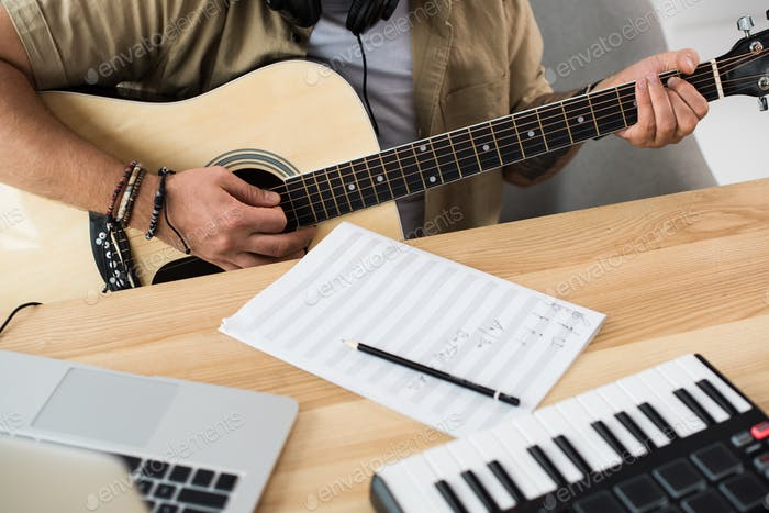 cropped shot of musician playing guitar at workplace with MPC pad and laptop