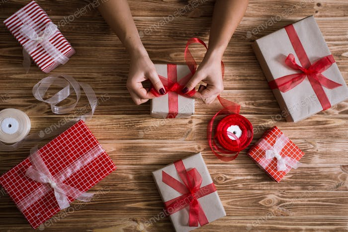 Female hands wrapping xmas gifts into paper and tying them up with red and white threads