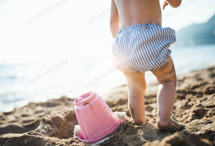 A midsection of small toddler girl with shorts playing on sand beach on holiday.