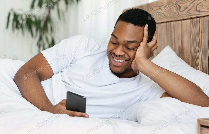 African Man With Smartphone Using Mobile App Lying In Bed