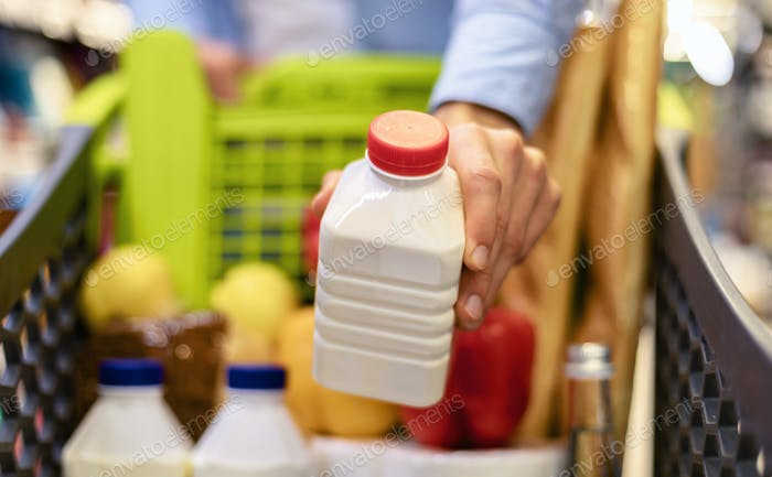 Closeup of man shopping groceries, buying milk
