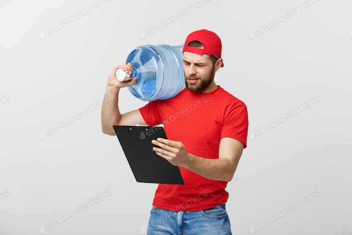 Portrait smiling bottled water delivery courier in red t-shirt and cap carrying tank of fresh drink