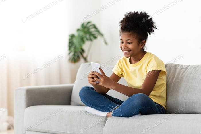 Black Kid Girl Playing Online On Smartphone Sitting At Home