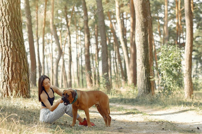 Girl sitting in a forest and playing with dog
